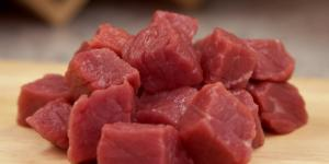 Cubed raw beef on a clean wood cutting board